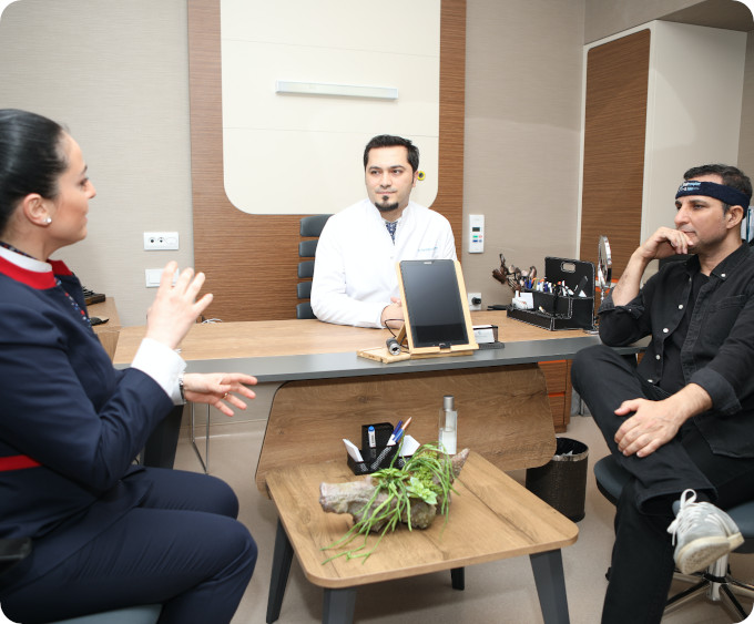 Dr. Balwi und Dolmetscher beraten Patienten zu Haartransplantation Berlin in einem Büro