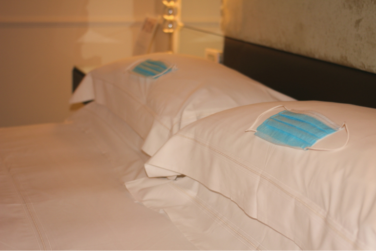 Nahaufnahme es desinfizierten Hotelbetts mit Mundschutzmasken auf den Kissen