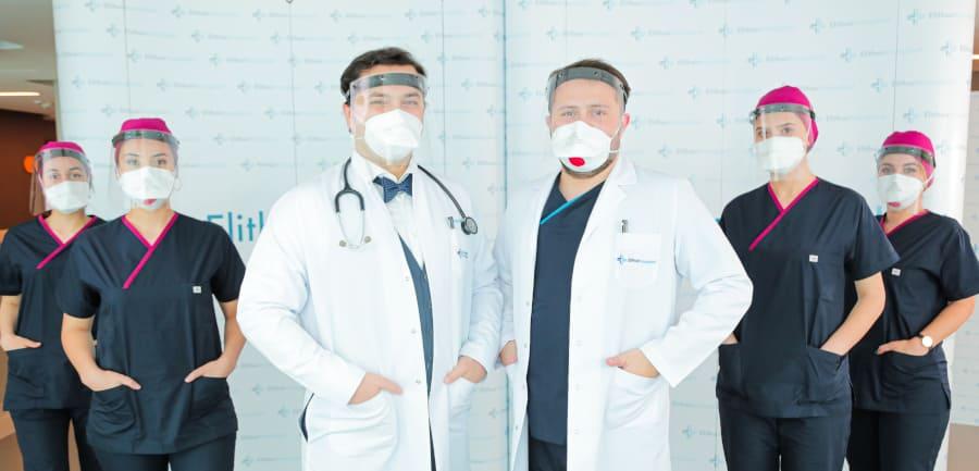 Dr. Balwi und sein Team stehen mit Mund und Nasenschutz vor einer Leinwand