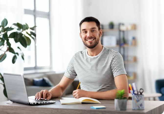 Junger Mann am Laptop lächelt in die Kamera, glücklich über Haartransplantation Finanzierung