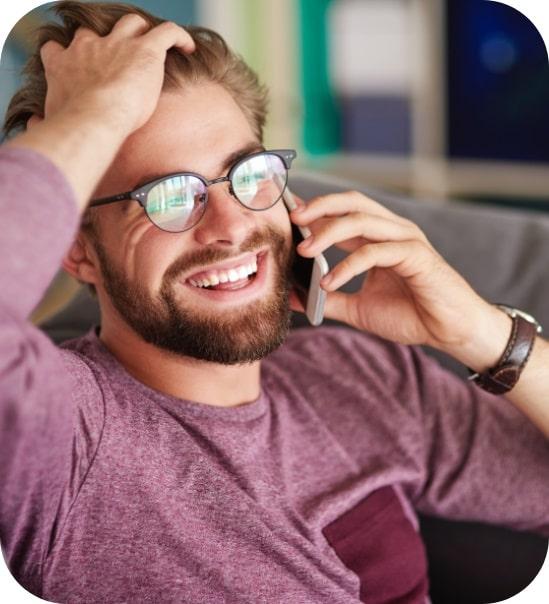 Lachender Mann mit Brille telefoniert