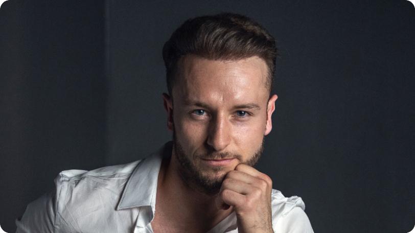Junger Mann mit vollem Haar und linker Hand am Kinn vor einem dunkelgrauen Hintergrund