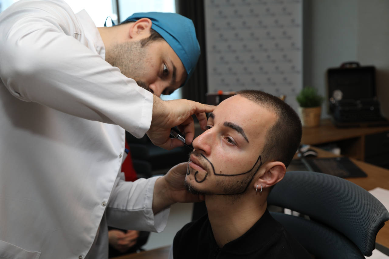 le dr balwi examine un patient souffrant d´une la pelade de barbe