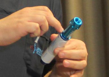 Détail des mains d'un expert Elithair insérant l'anesthésiant dans le dispositif sans aiguille