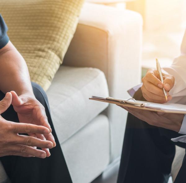 Gros plan sur les mains et les genoux d'un homme assis lors de la réunion préparatoire à une procédure de greffe de cheveux