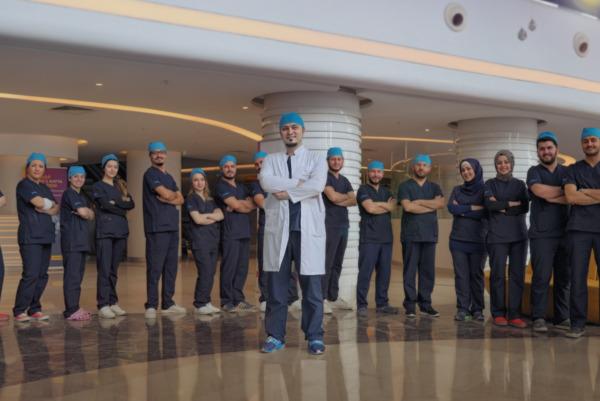 Photo en contre plongée du Dr Balwi entouré par son équipe