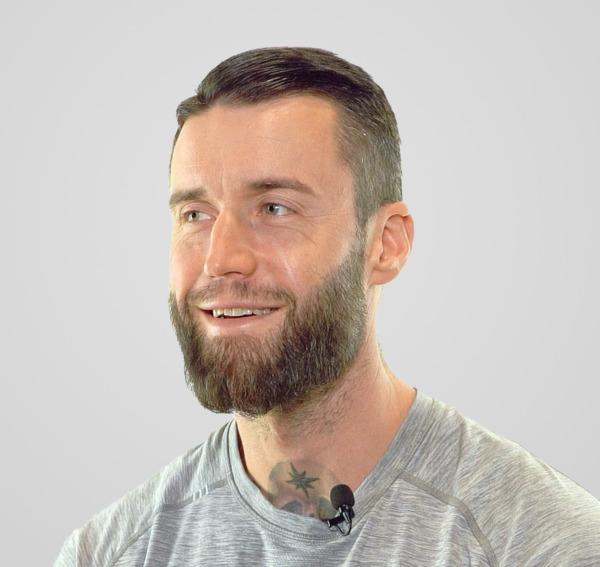 Un homme à la barbe fournie sourit