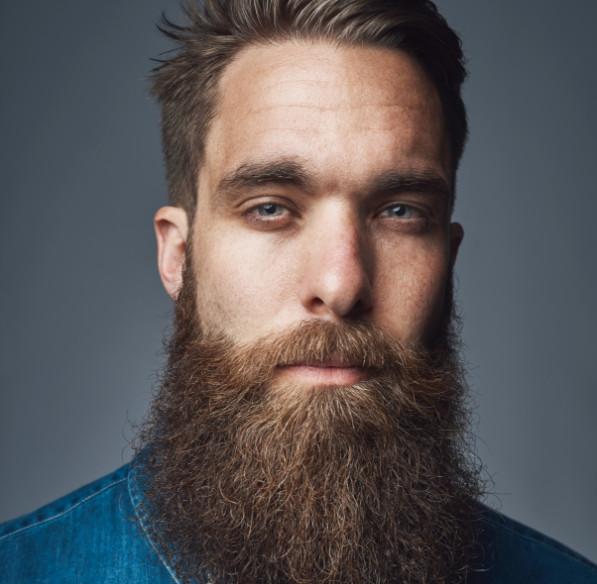 Un homme à la barbe restaurée regarde l'appareil photo