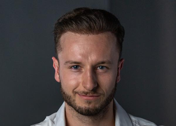Prise de vue du visage d'un homme souriant après une greffe de cheveux avec la méthode DHI
