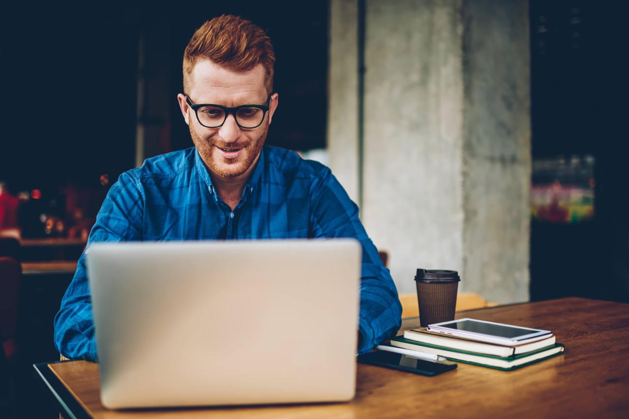 jeune homme souriant devant son PC après avoir découvert les solutions contre la calvitie