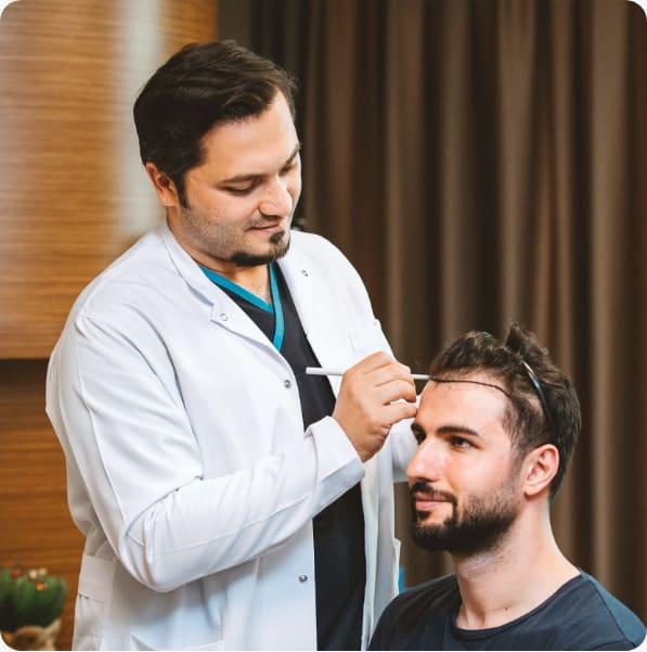 le Dr Balwi ausculte le cuir chevelu et dessine la nouvelle ligne capillaire d'un patient avant sa greffe de cheveux chez Elithair