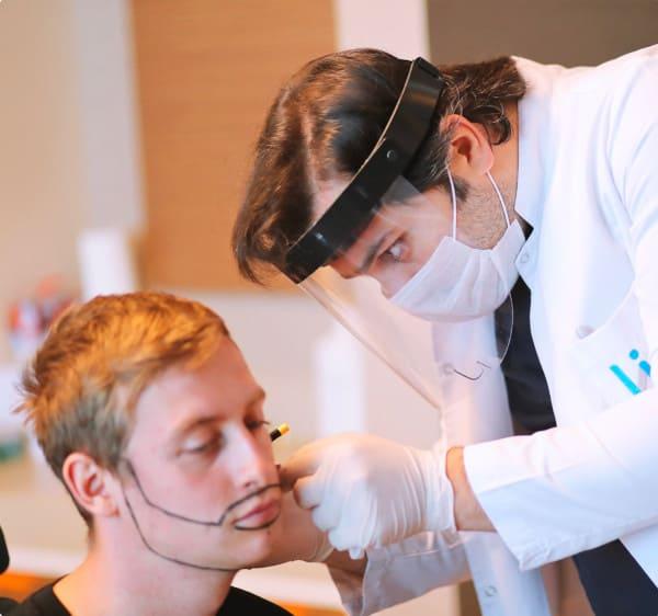 le dr balwi examinant un patient pour une greffe de barbe