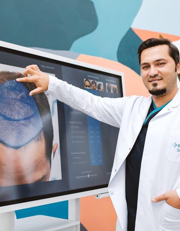 dr balwi montrant le crâne d'un patient afin de calculer le nombre de greffons nécéssaire
