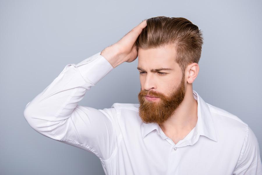 Mann mit Hand am Kopf will Haare schneller wachsen lassen
