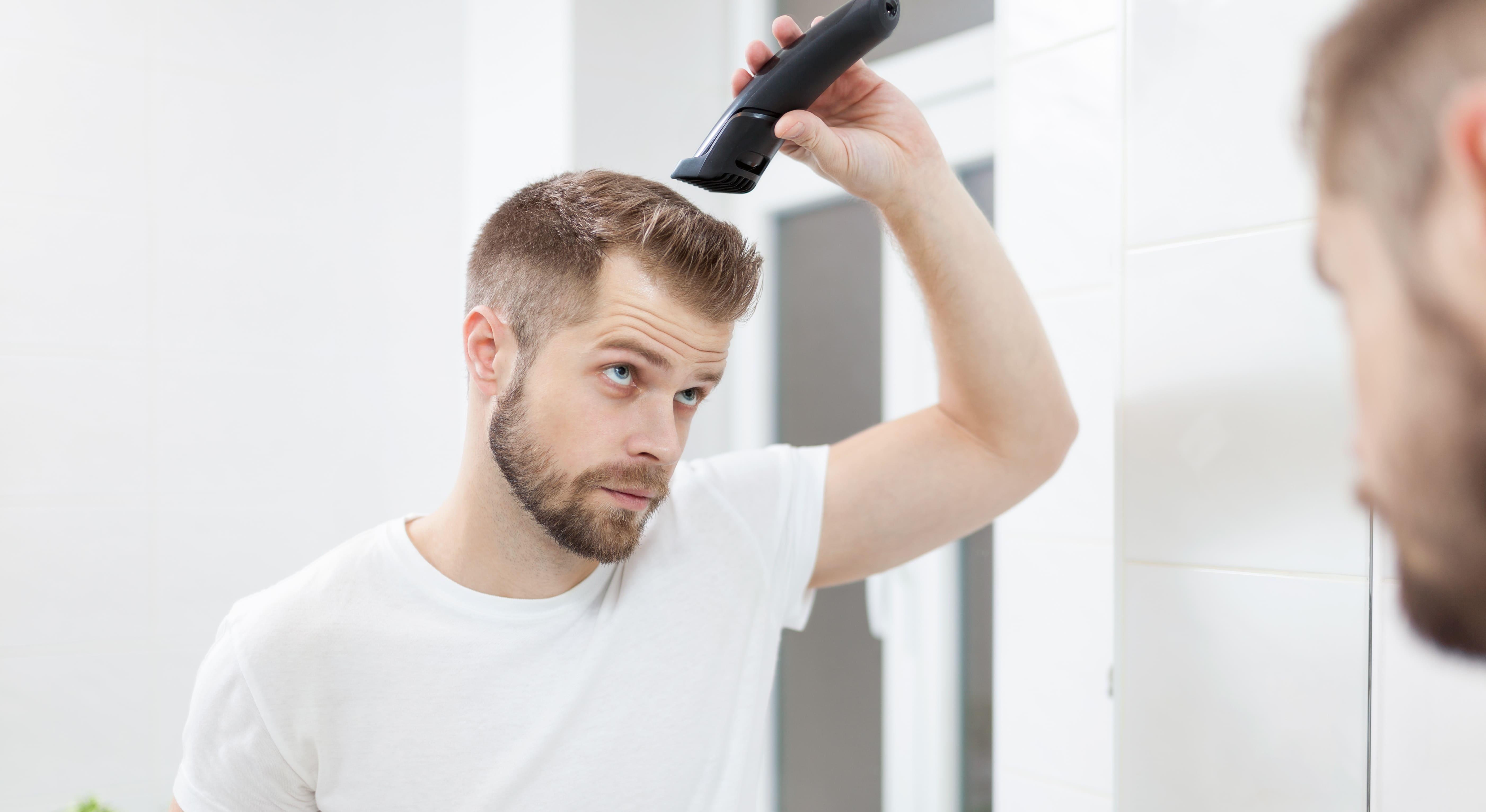 Haarkranz Frisur - gut aussehender Mann schneidet sich die Haare mit einem Haarschneider