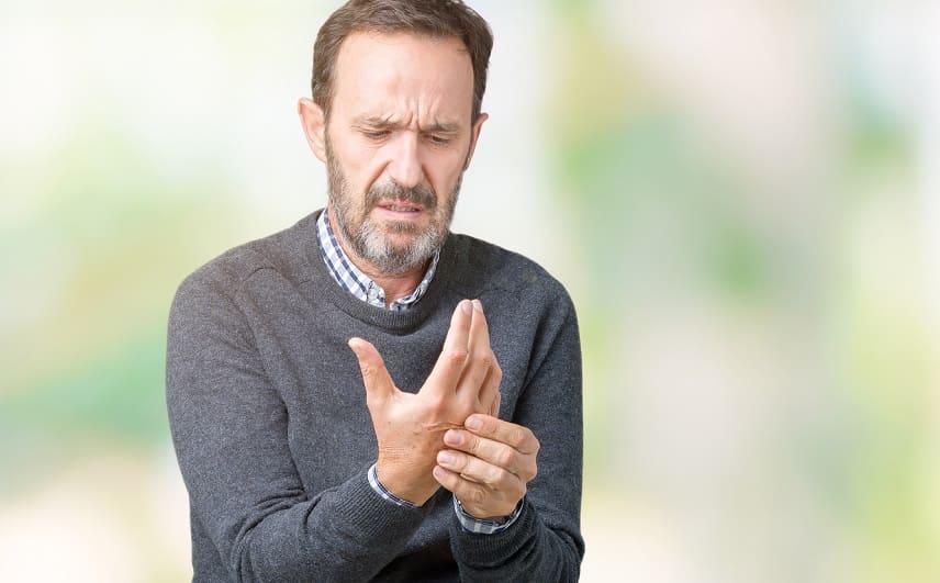 Haarausfall bei Rheuma - Junge Mann hat Handschmerzen