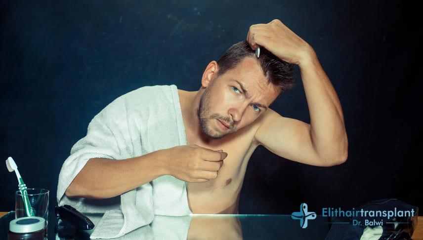 Haarausfall duch fettige Haare - Mann sieht sein Geheimratsecken
