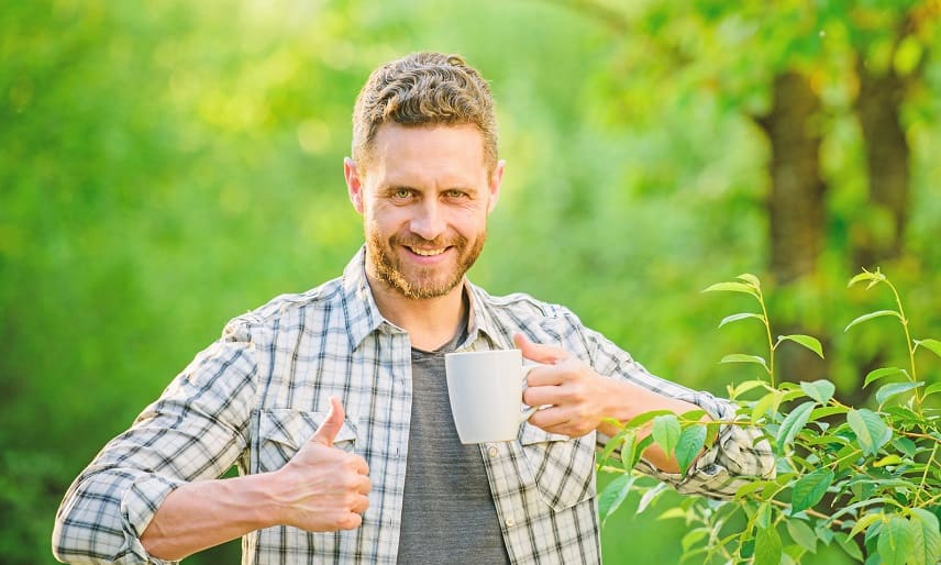 Gruene Tee gegen Haarausfall - Junge Mann trinkt Tee und zeigt die Daumen