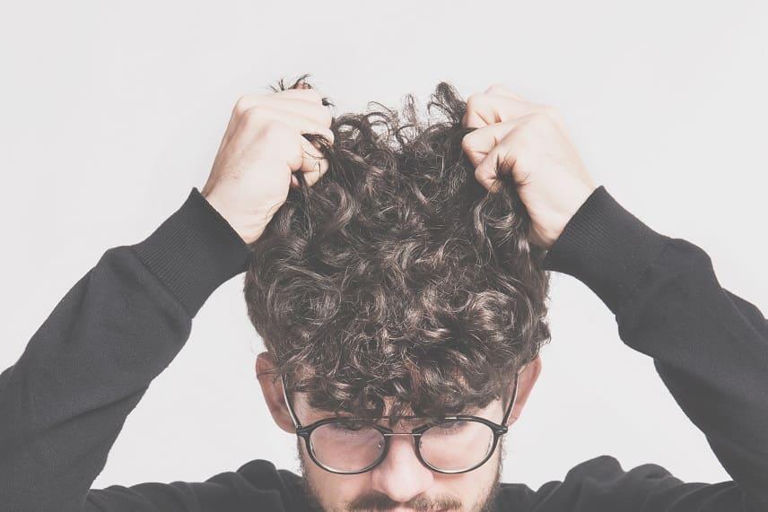 Trichotillomanie - Junge Mann mit Brille juckt seinen Kopf