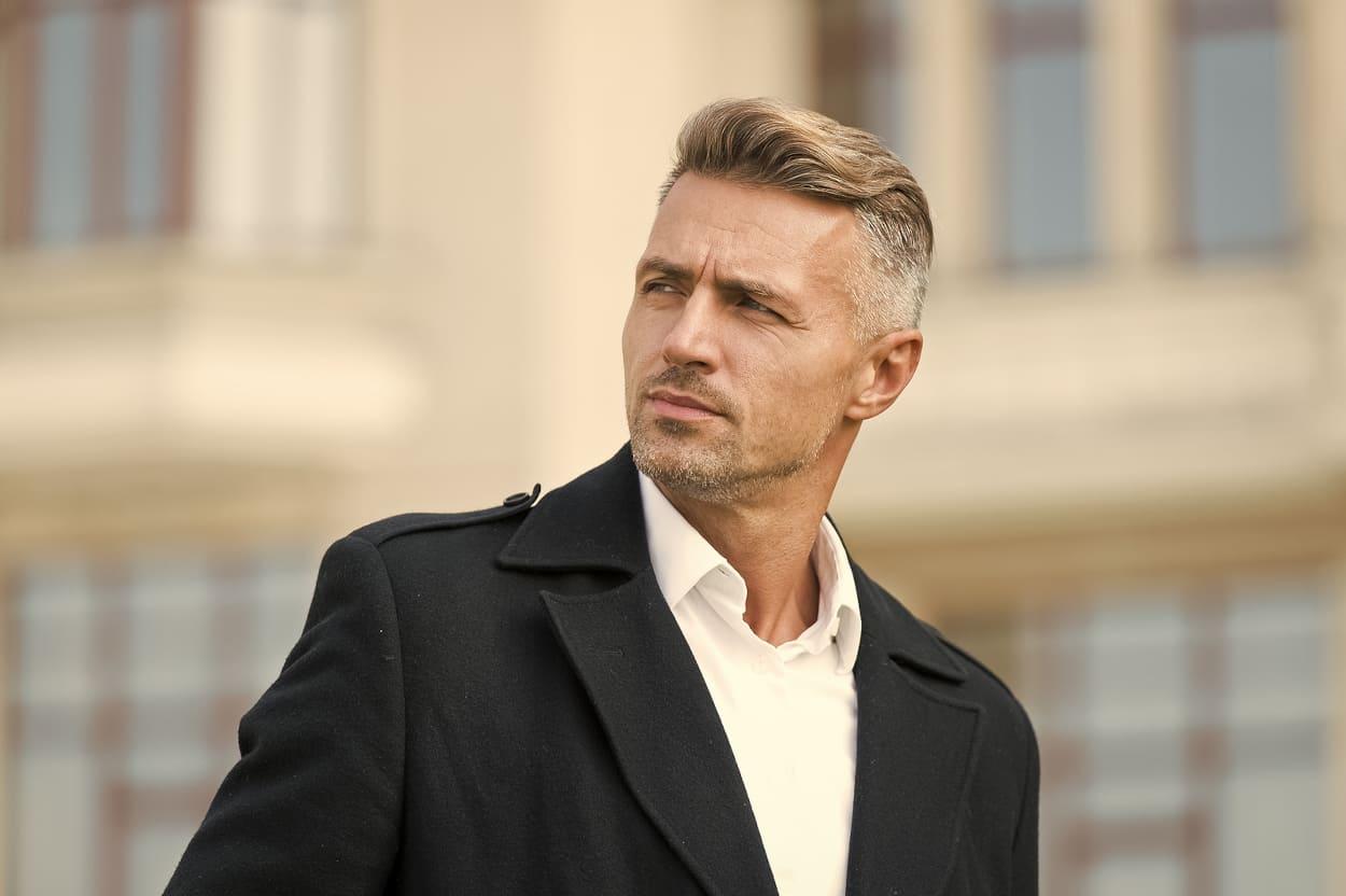 Mann steht vor einem Gebäude und schaut zur Seite