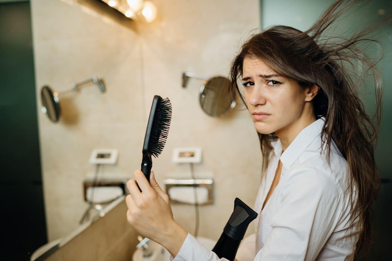 Frau mit Kamm und Föhn in der Hand vor einem Spiegel.