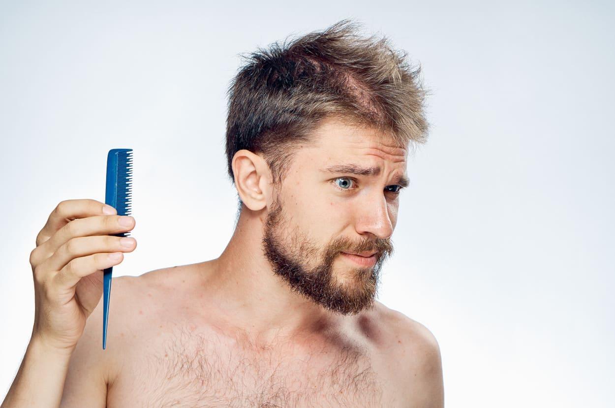 Mann kämmt sich die Haare und guckt verwundert.