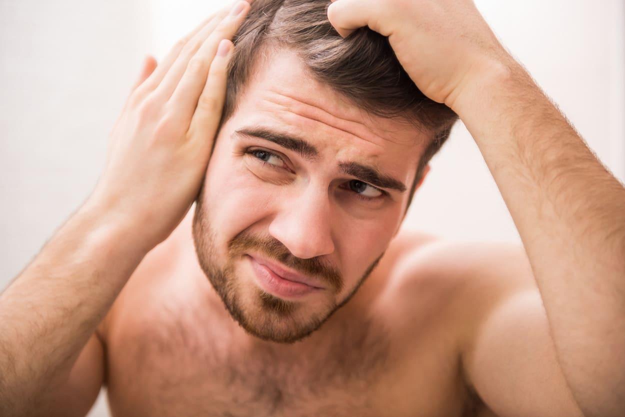 Mann hält sich die Haare und guckt dabei besorgt.