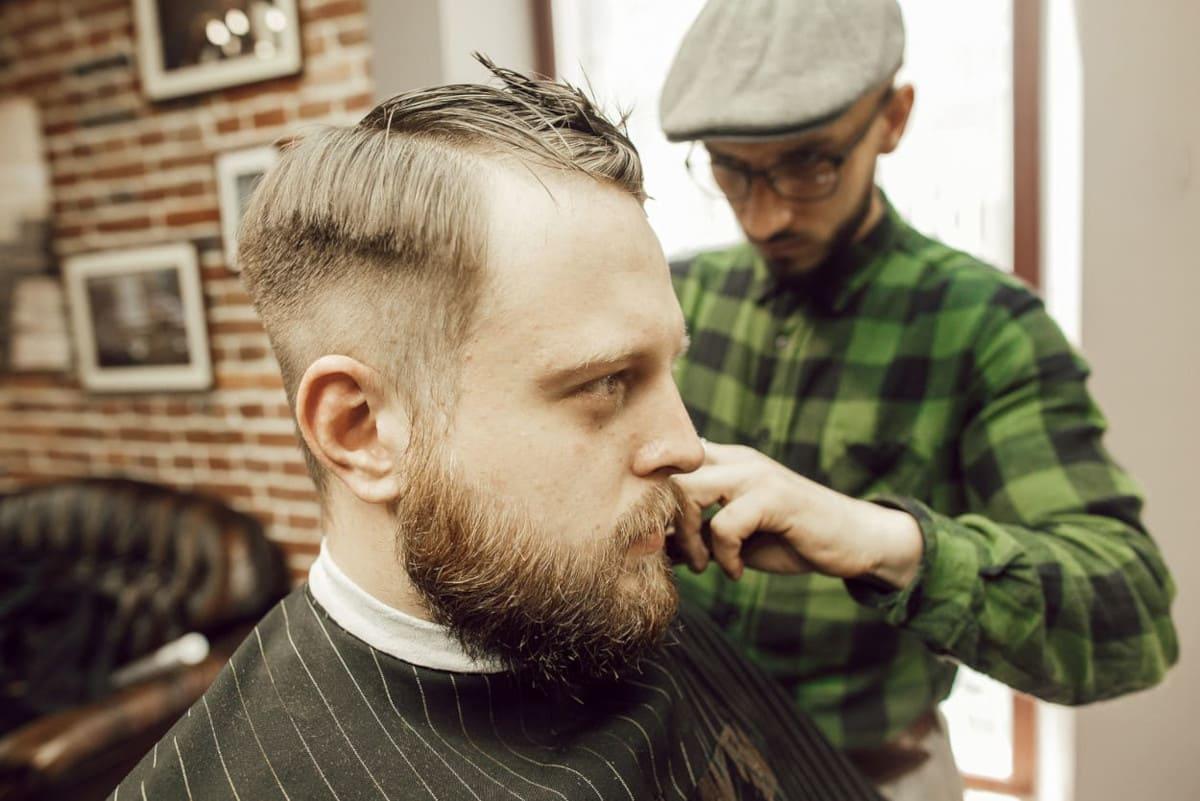 Mann lässt sich die Haare beim Friseur schneiden.