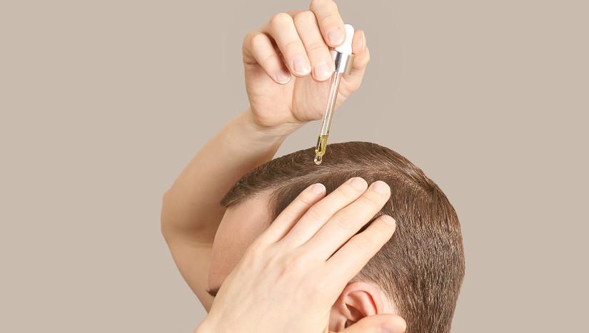 Mann benutzt Pipette, um seine Haare zu behandeln