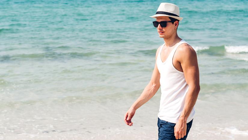 Mann läuft am Strand mit Hut.