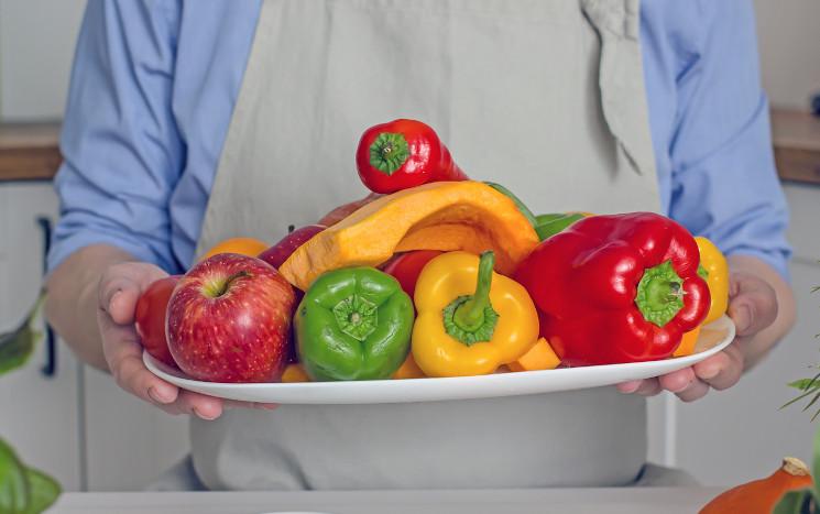 Mann hält Tablett mit Gemüse