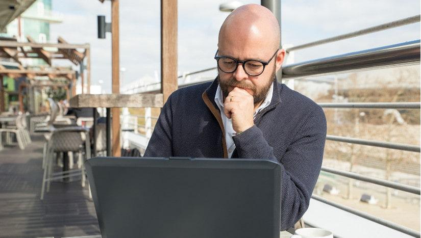 Mann mit Glatze guckt auf Laptop.