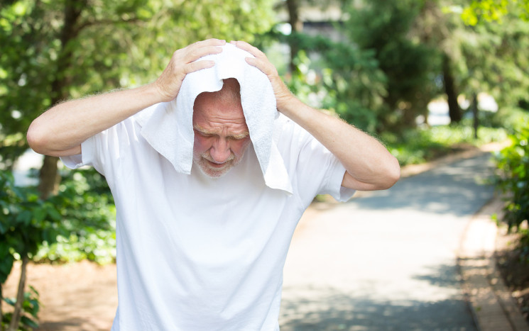 Mann trocknet Schweiß durch Sonne nach Haartransplantation von der Glatze
