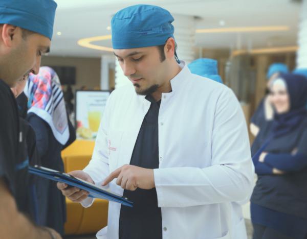 Dr. Balwi mit Kollegen am Tablet liest Artikel über DHI Haartransplantation