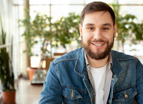 Junger Mann lächelnd nach seinem Eingriff mit der FUE Haartransplantation