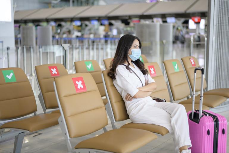 Viajero en aeropuerto, con señalizaciones en los asientos para mantener la distancia de seguridad durante el coronavirus.
