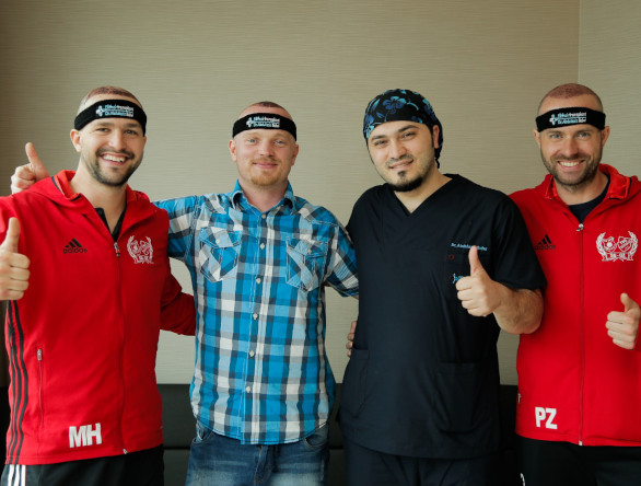 Le Dr Balwi en compagnie de trois patients satisfaits du résultat de leur greffe de cheveux