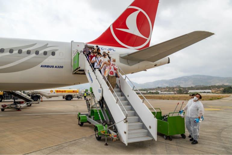 Pasajeros descendiendo de un avión de Turkish Airlines con personal de limpieza esperando en tierra.
