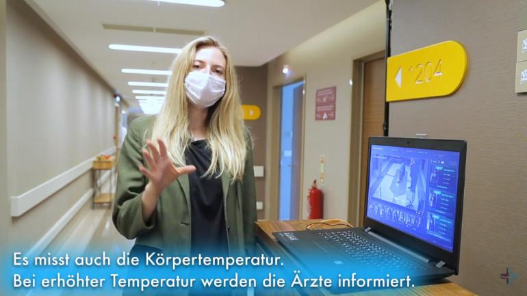 Selina explicando cómo funciona la medición de temperatura automatizada en el interior del hospital durante la crisis del coronavirus.