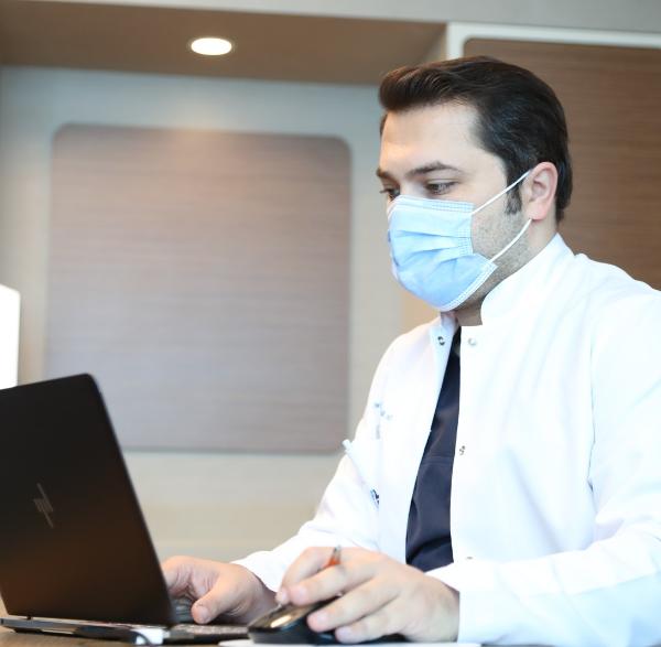 Le Dr Balwi prépare des documents sur la greffe de cheveux sur son ordinateur portable