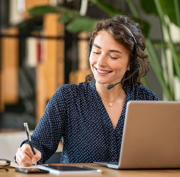 Lächelnde Frau am Telefon zur Vereinbarung eines Beratungsgesprächs zur Haartransplantation in Wien
