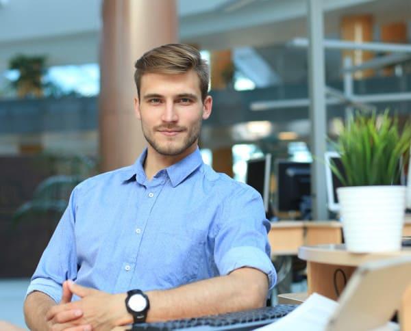 Blonder Mann lächelt stolz nach Haartransplantation in Berlin