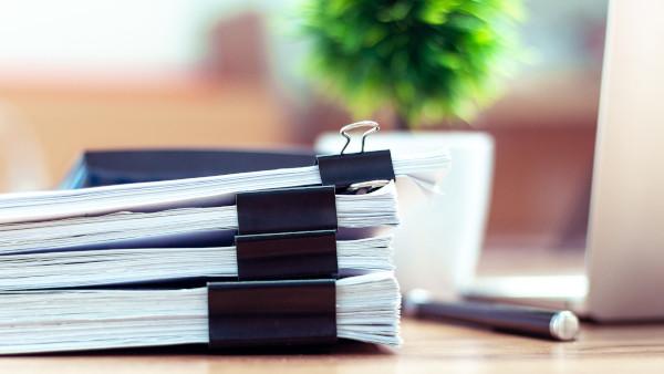 Ein Stapel an Unterlagen, auf einem Holztisch