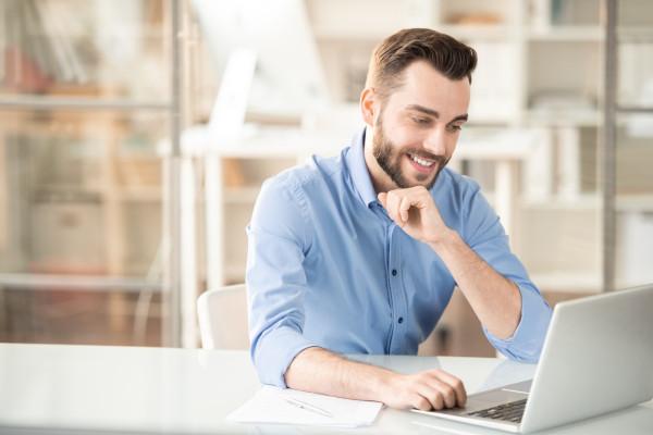 Mann sitzt am Laptop und berechnet die Haartransplantation Finanzierung