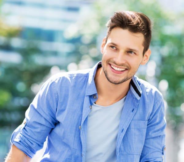 Lächelnder junger Mann in blauen Hemd nach Haartransplantation in Düsseldorf