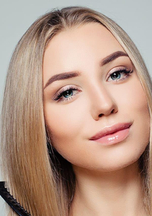 Blonde Frau kämmt sich die Haare nach Haartransplantation für Frauen