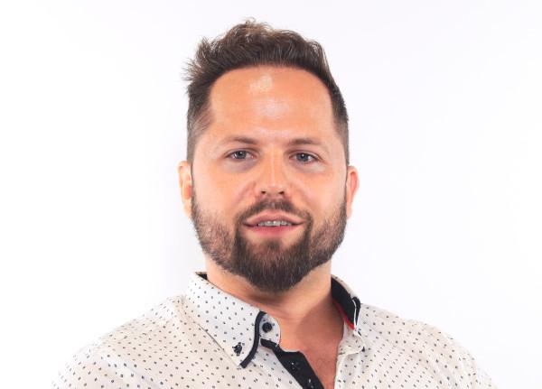 Mann nach Erfahrungen mit einer Haartransplantation lächelt in die Kamera
