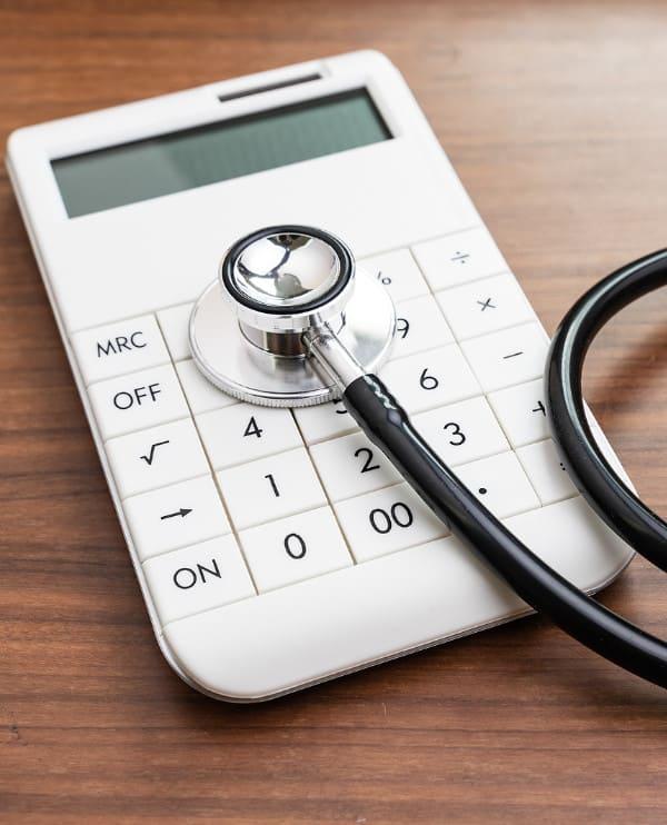 Taschenrechner mit Stethoskop auf einem braunen Tisch