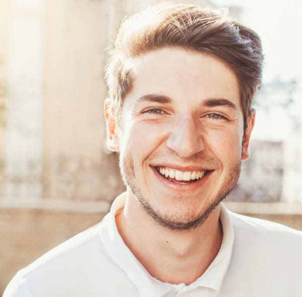 Junger Mann mit begeistertem Lächeln nach Haartransplantation in Wien