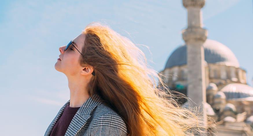 Frau mit Sonnenbrille in Istanbul schaut in die Sonne.